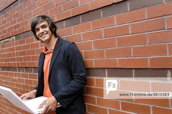Porträt eines jungen Mannes hält einen Laptop und lächelnd