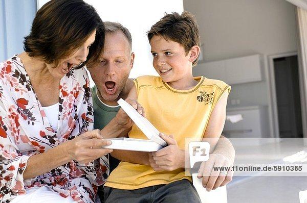 Geschenk geben lächeln Junge - Person Menschliche Eltern