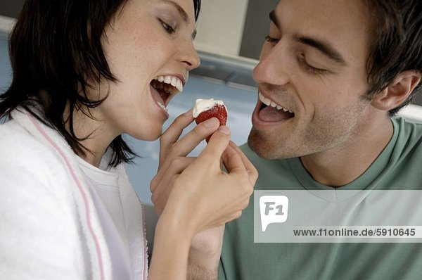 Close-up of a mid adult couple eating cherry