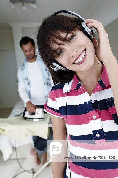 Portrait of a young woman listening to music with a young man ironing clothes behind her