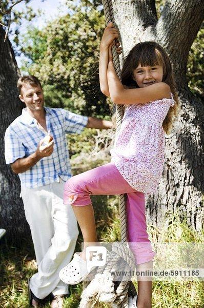 Profil  Profile  schaukeln  schaukelnd  schaukelt  schwingen  schwingt schwingend  Menschlicher Vater  Seil  Tau  halten  Hintergrund  Apfel  Seitenansicht  Mädchen  Schaukel