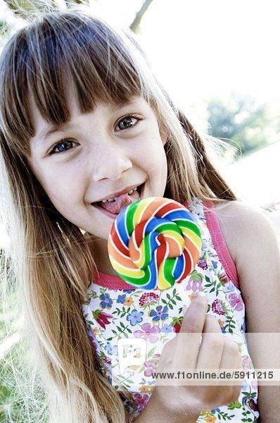 Portrait of a girl licking a lollipop