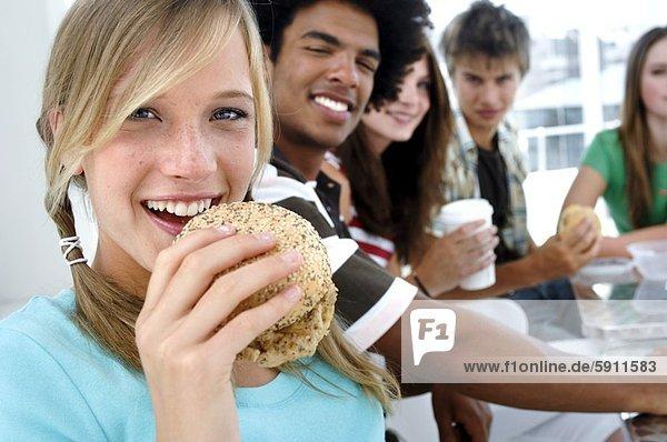hinter  sitzend  Portrait  Jugendlicher  Freundschaft  Hamburger  essen  essend  isst  Mädchen