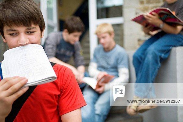 Close_up of a teenage boy holding a book. Close_up of a teenage boy holding a book