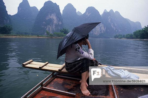 Profil  Profile  sitzend  Frau  Regenschirm  Schirm  halten  Boot  Seitenansicht  China