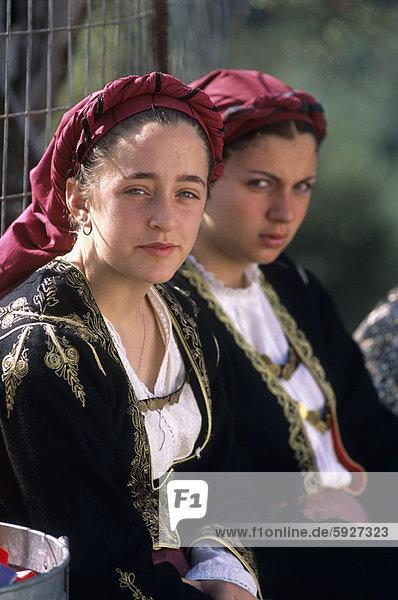 Portrait of two young women sitting side by side  Crete  Greece