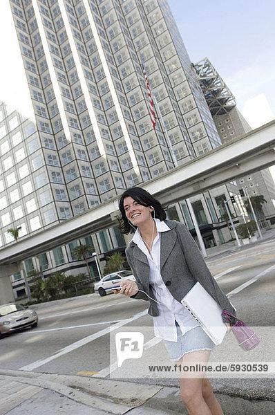 niedrig  Geschäftsfrau  zuhören  Notebook  tragen  Spiel  Ansicht  Flachwinkelansicht  MP3-Player  MP3 Spieler  MP3 Player  MP3-Spieler  Winkel