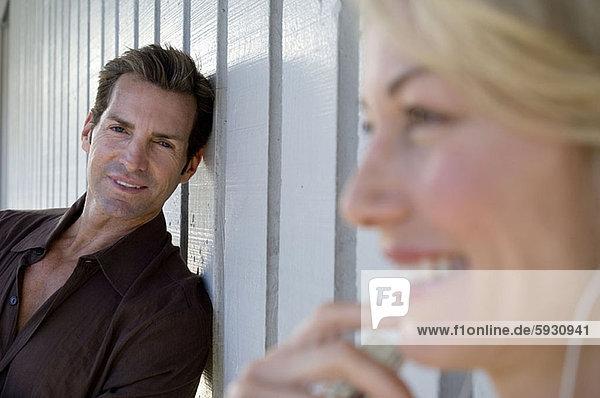 angelehnt  nebeneinander  neben  Seite an Seite  Portrait  Frau  Mann  Wand  lächeln  Mittelpunkt  Erwachsener