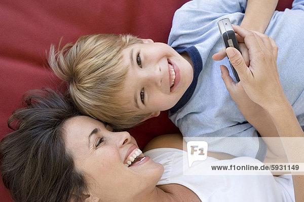 hoch  oben  liegend  liegen  liegt  liegendes  liegender  liegende  daliegen  Junge - Person  halten  Bett  Ansicht  Flachwinkelansicht  Mutter - Mensch  Winkel