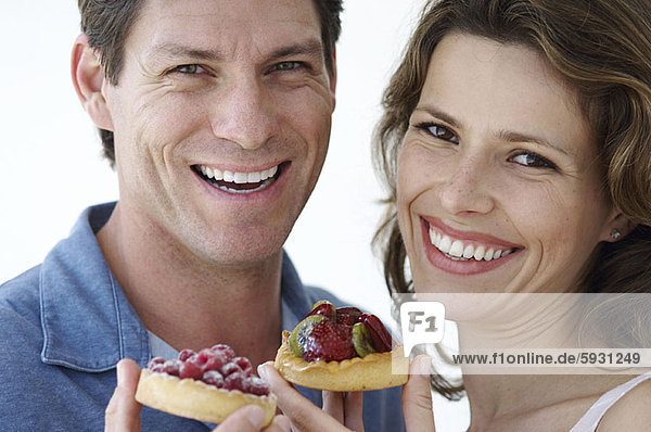 Portrait of a young couple holding pastries. Portrait of a young couple holding pastries
