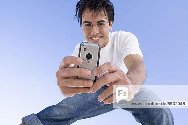 Handy  niedrig  Mann  Fotografie  nehmen  Kurznachricht  Ansicht  jung  Flachwinkelansicht  Winkel