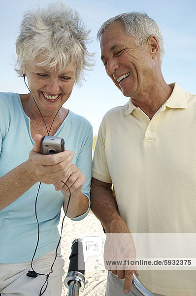 Close-up of a senior couple looking at a mobile phone and smiling. Close-up of a senior couple looking at a mobile phone and smiling