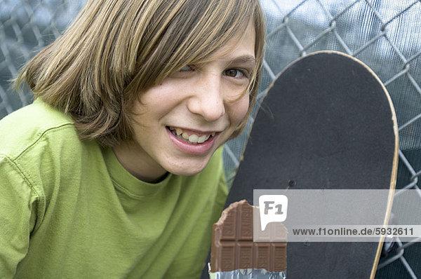 Portrait  Jugendlicher  Junge - Person  halten  Skateboard  Schokolade