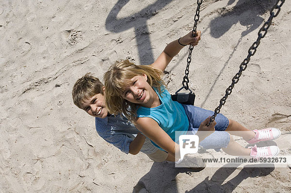 Portrait of a boy pushing a teenage girl on a swing. Portrait of a boy pushing a teenage girl on a swing