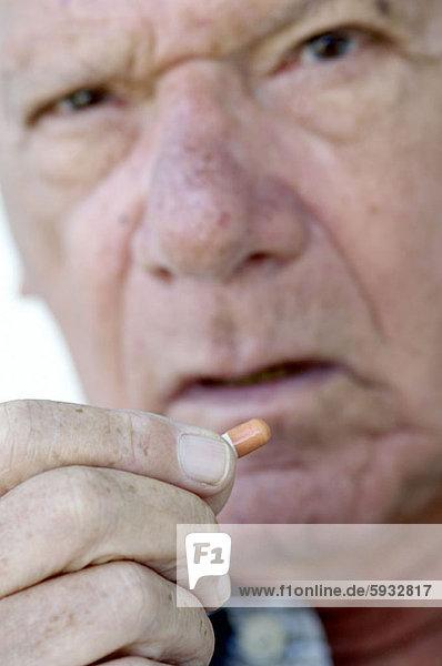 Portrait of a senior man holding a capsule. Portrait of a senior man holding a capsule