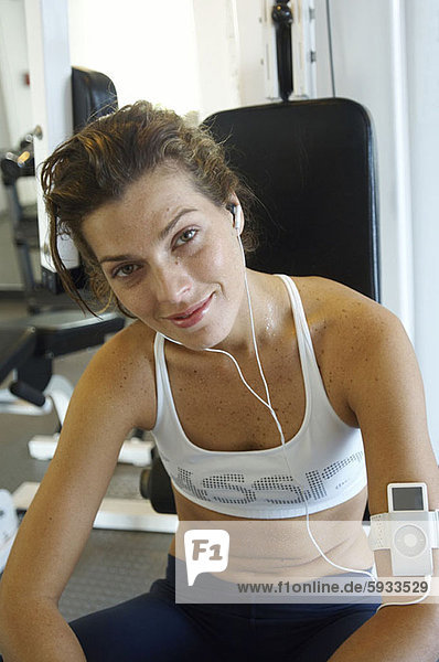 Portrait of a young woman sitting in a gym and listening to music on headphones. Portrait of a young woman sitting in a gym and listening to music on headphones