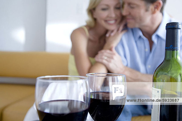 Close-up of two glasses of red wine and a bottle with a mid adult couple sitting in the background. Close-up of two glasses of red wine and a bottle with a mid adult couple sitting in the background
