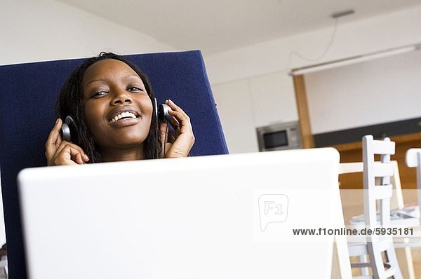 Portrait of a teenage girl listening to music on headphones and using a laptop. Portrait of a teenage girl listening to music on headphones and using a laptop