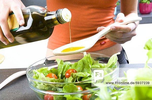 Anschnitt Frau eingießen einschenken Mittelpunkt Ansicht Holzlöffel Olive Öl