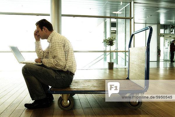 Profil Profile sitzend benutzen Mann Notebook Gepäck Fuhrwerk Mittelpunkt Seitenansicht Erwachsener