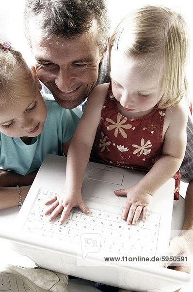 High angle view of a father and his two daughters using a laptop. High angle view of a father and his two daughters using a laptop