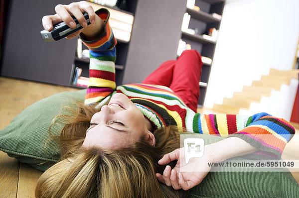 Handy liegend liegen liegt liegendes liegender liegende daliegen junge Frau junge Frauen halten Kopfkissen Kurznachricht