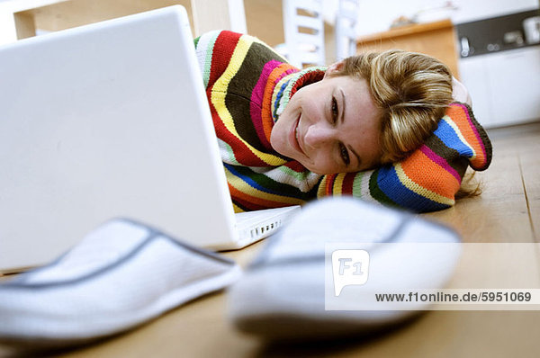 Portrait of a young woman lying on the floor in front of a laptop. Portrait of a young woman lying on the floor in front of a laptop