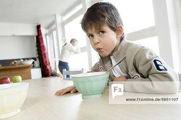 sitzend  Portrait  Junge - Person  am Tisch essen  frontal  Tisch