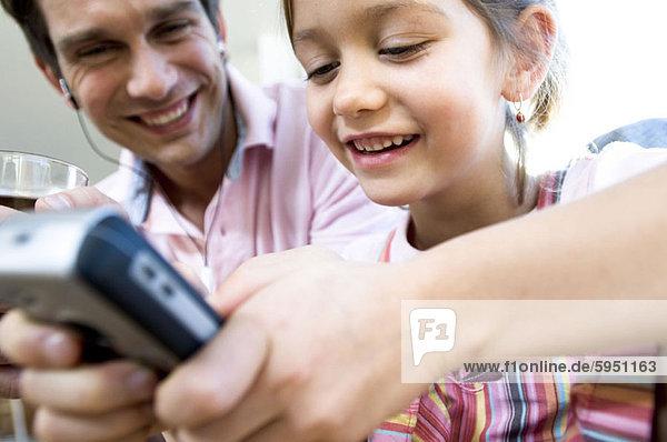 Handy  sitzend  nebeneinander  neben  Seite an Seite  benutzen  Menschlicher Vater  Close-up  close-ups  close up  close ups  Kurznachricht  Tochter