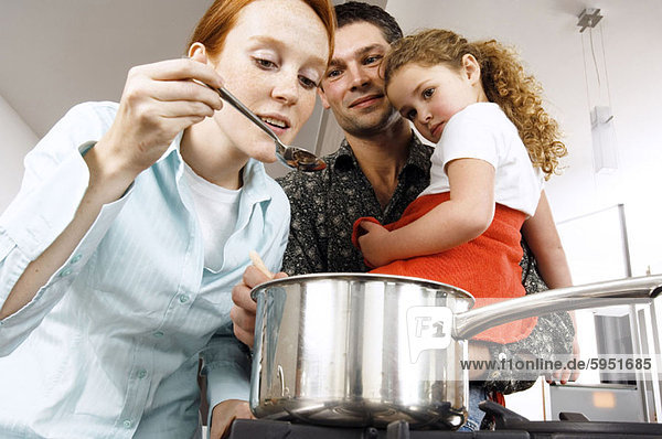 Parents and their daughter looking at a spoon. Parents and their daughter looking at a spoon
