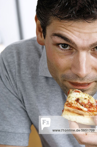 Close-up of a young man eating a slice of pizza. Close-up of a young man eating a slice of pizza