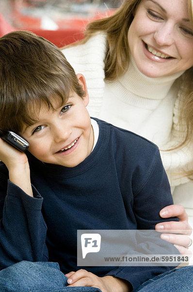 Handy  sitzend  benutzen  Portrait  Sohn  Kurznachricht  Mutter - Mensch