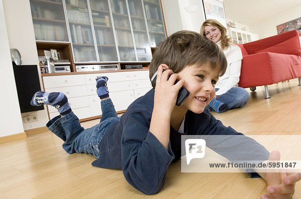 Side profile of a boy using a mobile phone with his mother sitting beside him. Side profile of a boy using a mobile phone with his mother sitting beside him