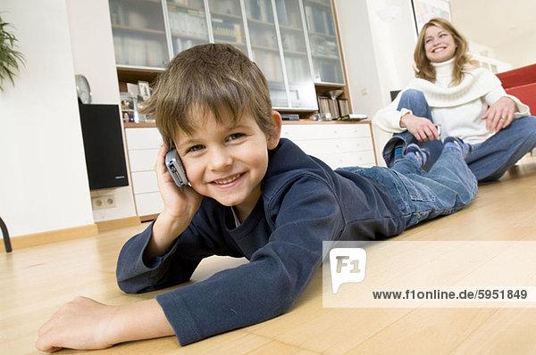 Handy hinter sitzend benutzen Portrait Sohn Kurznachricht Mutter - Mensch