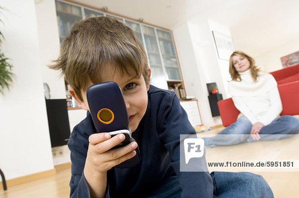 Handy hinter sitzend Portrait Sohn halten Kurznachricht Mutter - Mensch