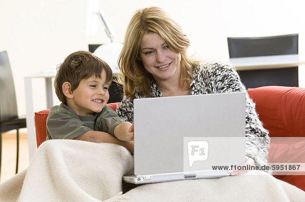 Mother sitting with her son and using a laptop. Mother sitting with her son and using a laptop