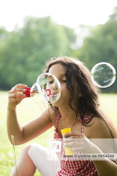 Mädchen macht Seifenblasen auf einer Wiese