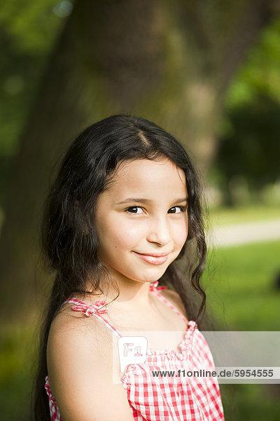 Lächelndes dunkelhaariges Mädchen im Freien  Portrait