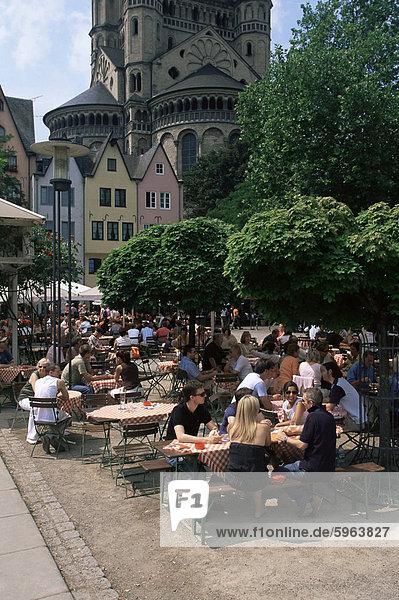 Leute sitzen in einem Restaurant im Freien  in der Nähe von St. Martin-Kirche  die über den Fischmarkt in der alten Stadt  Köln  Nord Rhein Westfalen  Deutschland  Europa steigt Leute sitzen in einem Restaurant im Freien, in der Nähe von St. Martin-Kirche, die über den Fischmarkt in der alten Stadt, Köln, Nord Rhein Westfalen, Deutschland, Europa steigt