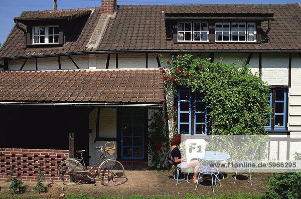 Außenaufnahme Frankreich Europa Frau Wohnhaus typisch Tisch vorlesen