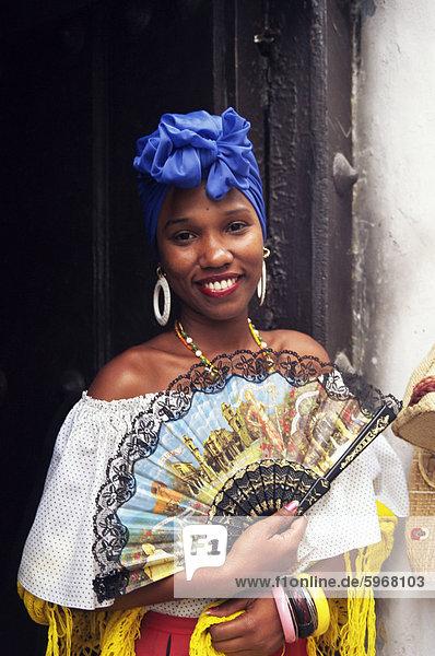 Junge Frau im typischen kubanischen Kleid hält eine Fan  Habana Vieja  Havanna  Kuba  Westindische Inseln  Mittelamerika