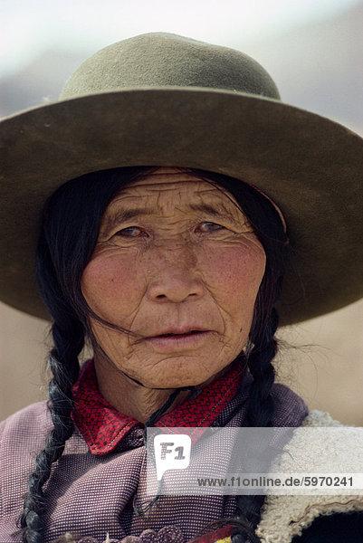 Porträt einer tibetischen Frau mit Zöpfen und Hut auf dem Qinghai-Plateau  China  Asien