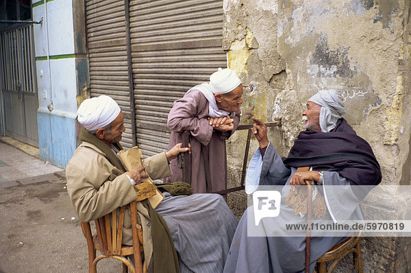 Three old men outside talking in a street in Cairo  Egypt  North Africa  Africa