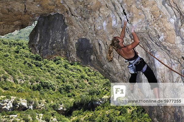 Eine Frau auf einem überhängenden durchqueren Klettern auf den berühmten Kalksteinfelsen der Mascun Canyon  Rodellar  Sierra de Guara  Aragon  südliche Pyrenäen  Spanien  Europa