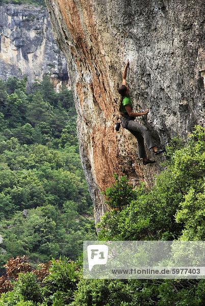 Eine Frau greift einen sehr schwierigen Aufstieg auf den Kalksteinfelsen nahe Siuarana  ein mittelalterliches Dorf in der Nähe von Reus und Barcelona  Katalonien  Spanien  Europa
