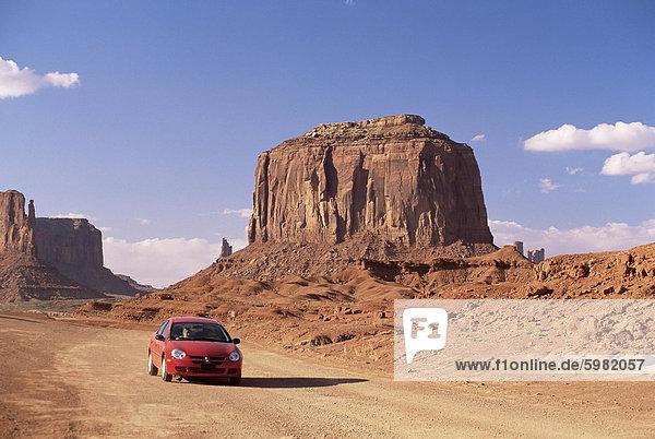 Auto auf Laufwerk Talstrasse unter Merrick Butte  Monument Valley  Arizona/Utah Grenze  Vereinigte Staaten von Amerika  Nordamerika