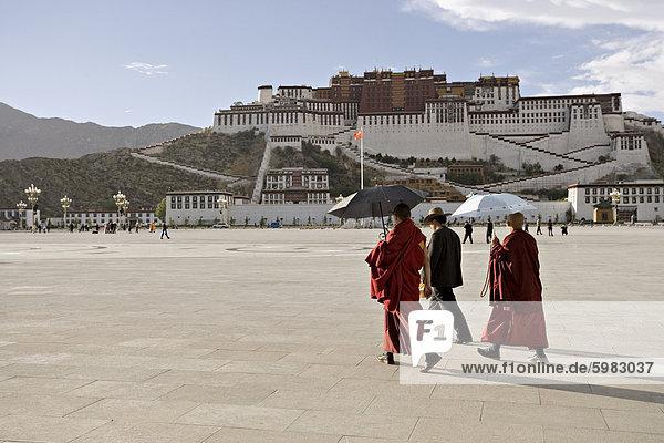 Mönche tragen Schirme gegen die Sonne  vor dem Potala-Palast  UNESCO-Weltkulturerbe  abschirmen  Lhasa  Tibet  China  Asien
