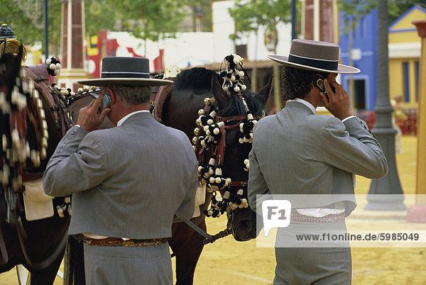 Männer in traditioneller Kleidung  die Benutzung von Mobiltelefonen  Feria del Caballo (Horse Fair)  Jerez De La Frontera  Cadiz-Bereich  Andalusien (Andalusien)  Spanien  Europa