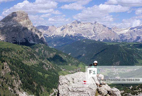 Wanderer ruht auf Alta Via Dolomiti (Via Ferrata) Wanderweg mit Corvara Dorf unten  Dolomiten  Südtirol  Italien  Europa