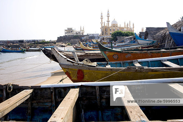 Fishing boats with a mosque in the background  Vizhinjam  Trivandrum  Kerala  India  Asia